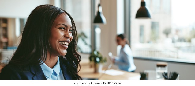 Young African American businesswoman laughing while walking in an office after a meeting with colleagues