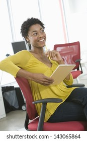 Young African American businesswoman with notepad and pencil sitting on office chair