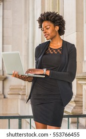 Young African American Businesswoman with short afro hairstyle, wearing fashionable work clothes, standing in vintage office building in New York, working on laptop computer.