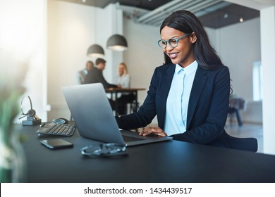 Young African American businesswoman smiling while sitting at her desk in a bright modern office working online with a laptop with coworkers in the background