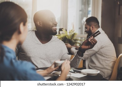 Young African American is calculated credit card. A smiling African American man is paying for an order in a cafe with a credit card. The concept of restaurant business and customer service.