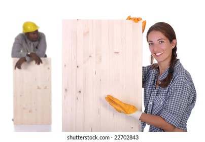 Young african american carpenter and woman carpenter holding wooden plank