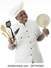 A young African American chef happily displaying some of his utensils and a small frying pan.  On a white background.
