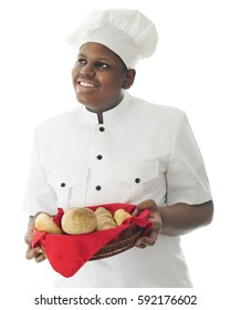 A young African American chef looking up as he carries a basket with a variety of breads.  On a white background.