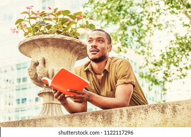 Young African American College Student studying in New York, wearing green short sleeve shirt, standing, back bending forward on top of wall on campus, hands holding red book, looking up, thinking.