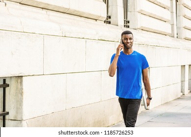 Young African American college student studying in New York, wearing blue T suit, black pants,  holding laptop computer, talking on cell phone, walking on street outside office building on campus.