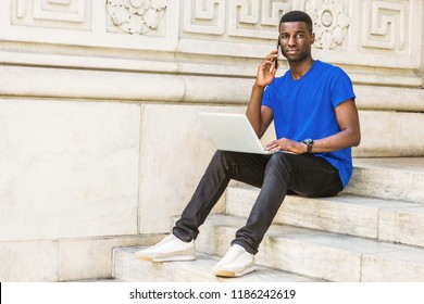 Young African American College Student studying in New York, wearing blue T shirt, black pants, sneakers, wristwatch, sitting on stairs on campus, working on laptop computer, talking on cell phone.