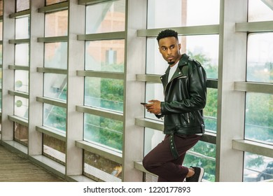 Young African American College Student with beard, afro short hair, wearing black leather jacket, standing against glass wall on campus in New York, texting on cell phone, looking away, thinking.