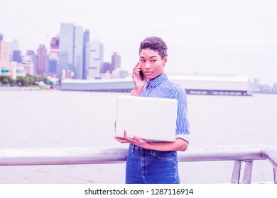 Young African American college student working in New York, wearing striped shirt, jeans, standing by Hudson River, holding laptop computer, talking on cell phone. Color Proton Purple filtered look.