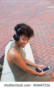 Young african american college student on campus looking at her cell phone and has head phones on