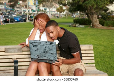 a young african american couple are shocked at what they find while using a laptop computer outside