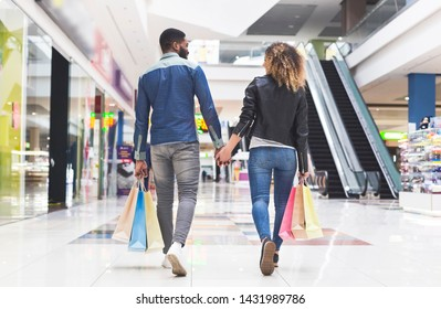 Young african american couple with shopping bags walking by mall center holding hands, panorama, back view, copy space