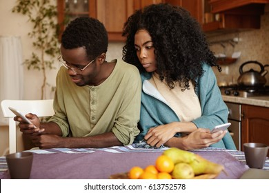 Young African American couple using electronic gadgets at home: happy husband browsing newsfeed via social networks while his jealous possessive wife spying, trying to see whose pictures he is liking