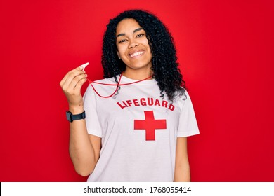 Young african american curly lifeguard woman wearing t-shirt with red cross using whistle with a happy face standing and smiling with a confident smile showing teeth