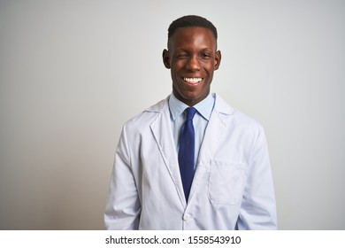 Young african american doctor man wearing coat standing over isolated white background winking looking at the camera with sexy expression, cheerful and happy face.