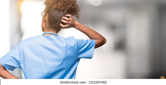 Young african american doctor woman over isolated background Backwards thinking about doubt with hand on head