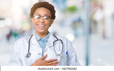 Young african american doctor woman wearing medical coat over isolated background Smiling and laughing hard out loud because funny crazy joke. Happy expression.