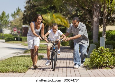 A young African American family with boy child riding his bicycle and his happy excited parents giving encouragement next to him