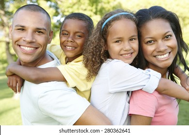 Young African American Family Relaxing In Park