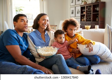 Young African American family sitting together on the sofa in their living room watching TV and eating popcorn