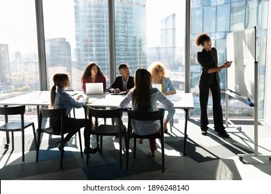 Young African American female coach or speaker make flip chart presentation to diverse businesspeople at meeting in office. Woman tutor or trainer present project on whiteboard to diverse colleagues.