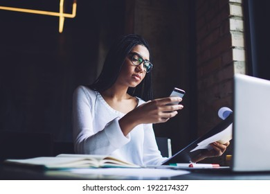Young African American female freelancer in glasses messaging on mobile phone while sitting at table with documents and laptop in modern workspace