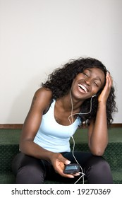 Young African American Female Sitting Down Listening to Music Player