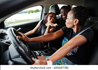 Young african american friends sitting inside a car.