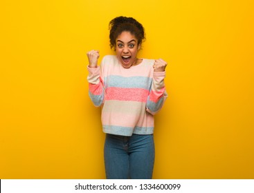 Young african american girl with blue eyes surprised and shocked
