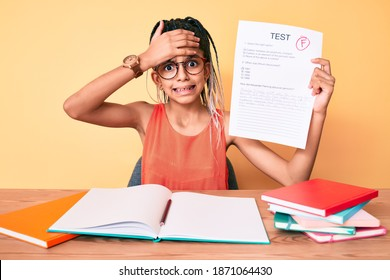 Young african american girl child with braids showing failed exam stressed and frustrated with hand on head, surprised and angry face
