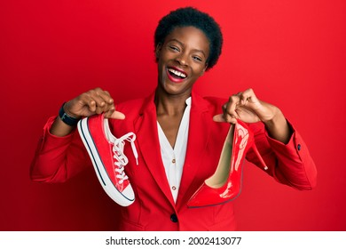 Young african american girl choosing high heel shoes and sneakers smiling and laughing hard out loud because funny crazy joke.