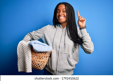 Young african american girl doing domestic housework holding laundry wicker basket surprised with an idea or question pointing finger with happy face, number one