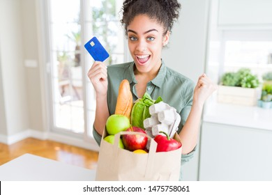 Young african american girl holding paper bag of groceries and credit card as payment screaming proud and celebrating victory and success very excited, cheering emotion