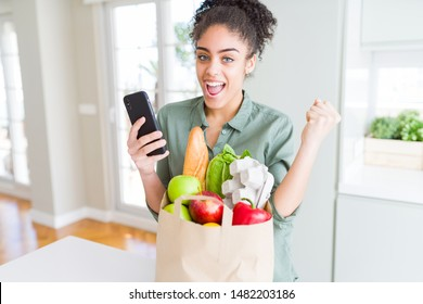 Young african american girl holding paper bag of groceries and using smartphone screaming proud and celebrating victory and success very excited, cheering emotion