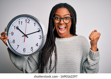 Young african american girl holding big minute clock over isolated background screaming proud and celebrating victory and success very excited, cheering emotion