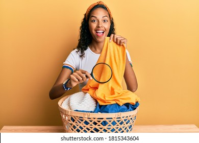 Young african american girl holding magnifying glass looking for stain at clothes celebrating crazy and amazed for success with open eyes screaming excited.  - Shutterstock ID 1815343604