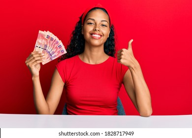 Young african american girl holding south african 50 rand banknotes sitting on the table smiling happy and positive, thumb up doing excellent and approval sign