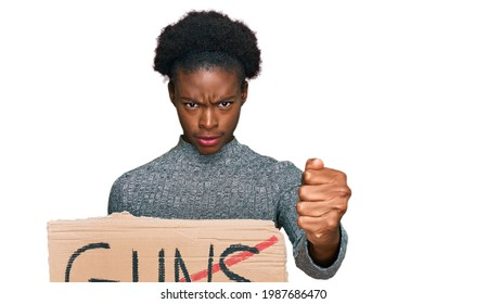 Young african american girl holding no guns warning banner annoyed and frustrated shouting with anger, yelling crazy with anger and hand raised
