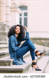 Young african american girl in jeans posing near old building
