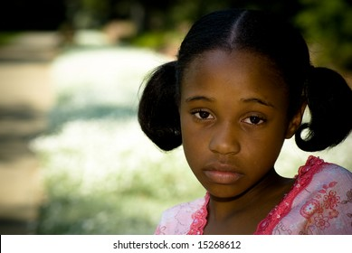 a young african american girl looks sad in the park.