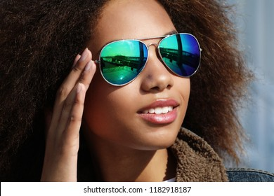 Young african american girl in sunglasses, posing outdoors, Dressed casul, with short voluminous hair.