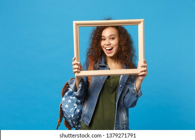 Young african american girl teen student in denim clothes, backpack hold frame isolated on blue background studio portrait. Education in high school university college concept. Mock up copy space