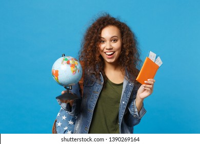Young african american girl teen student in denim clothes, backpack hold pass isolated on blue wall background studio portrait. Education in high school university college concept. Mock up copy space