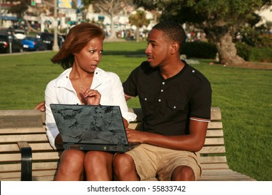 a young african american girl is upset at her boyfriend with what she finds while using a laptop computer outside