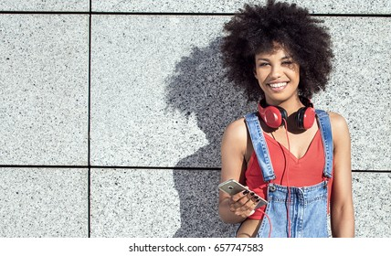Young african american girl using mobile phone and headphones, smiling.