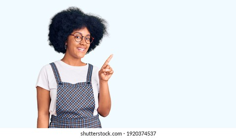Young african american girl wearing casual clothes showing and pointing up with finger number one while smiling confident and happy.