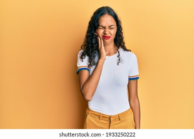 Young african american girl wearing casual clothes touching mouth with hand with painful expression because of toothache or dental illness on teeth. dentist
