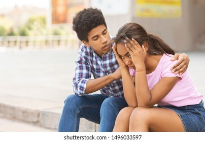 Young african american guy comforting his sad girlfriend after arguing on public.
