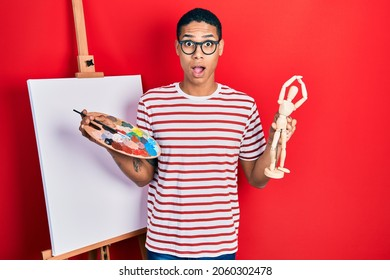 Young african american guy holding painter palette and art manikin afraid and shocked with surprise and amazed expression, fear and excited face.