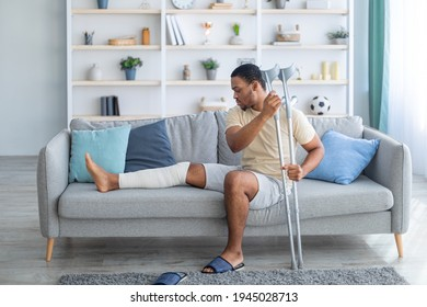 Young African American guy with plastered leg sitting on sofa, leaning on crutches at home. Millennial black man suffering from pain in broken limb, resting on couch, full length portrait